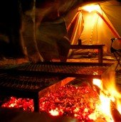 """Moving at lightening speed cooking dinner, I watch the art of """"Braai"""" (South African BBQ) from Caine in camp."""