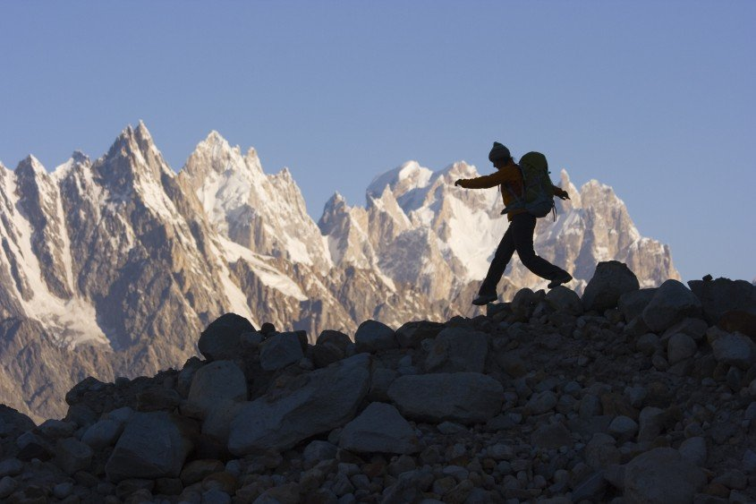 A silhouette of a woman hiker on the Biafo glacier in the Karakoram Himalaya in Pakistan