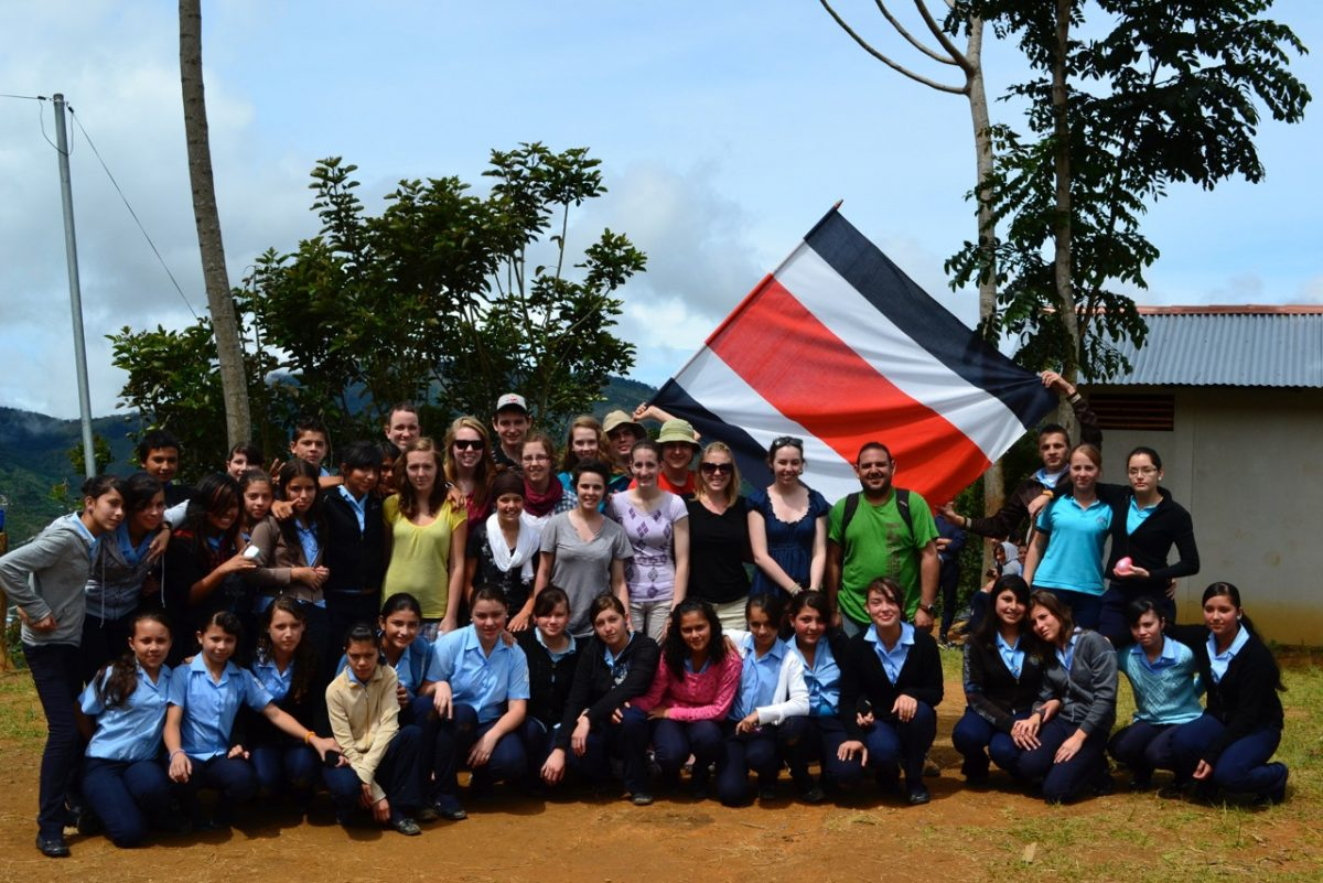 High School volunteer trip in Costa Rica 2011. Picture of our group with local students with the Costa Rican flag, where my passion for travel all started. Photo from Rachel Whalen.